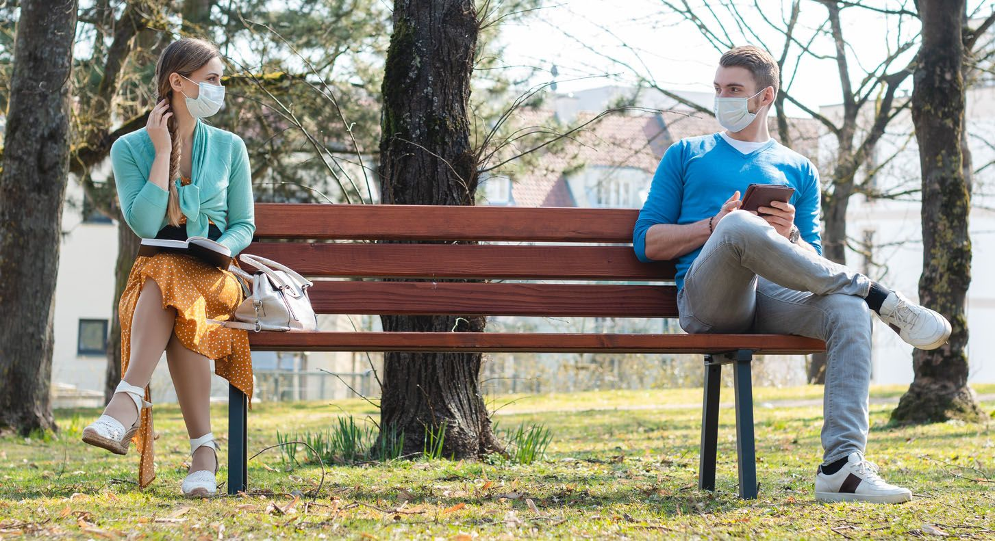 A female and male sitting on a bench wearing masks maintaining distance.